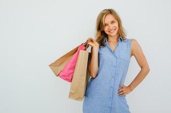 Улыбающаяся симпатичная женщина, держащая сумки для покупок