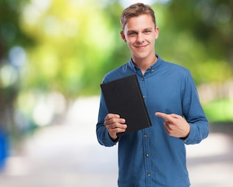 Smiling man holding a black notebook