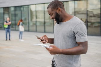 Smiling man with phone and papers