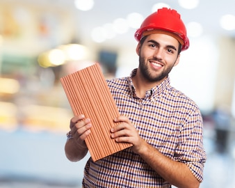 Smiling man with red helmet and a brick