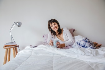 Smiling modern woman in bed with coffee