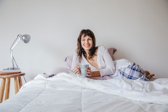 Smiling modern woman with coffee on bed