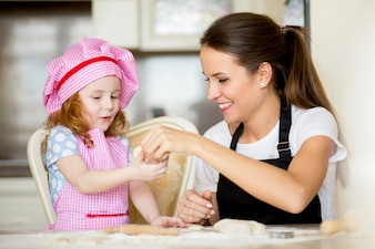 Smiling mother giving dough to little daughter