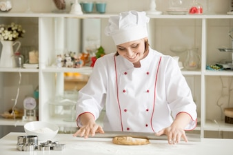 Smiling professional confectioner rolling gingerbread dough