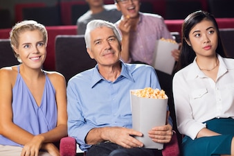 Smiling senior man watching movie in cinema