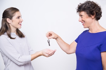 Smiling senior mother giving keys to daughter