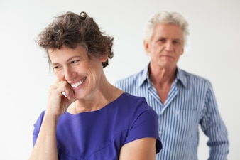 Smiling Senior Woman and Husband Standing Behind