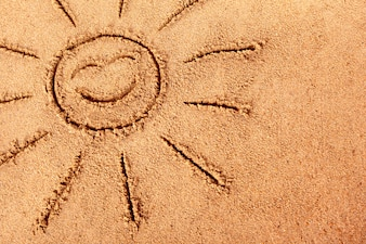 Smiling sun drawn on a sandy beach