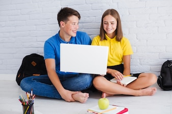Smiling teenagers using laptop