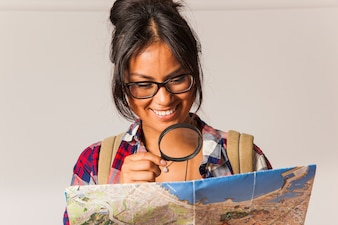Smiling tourist woman using magnifying glass to look at map