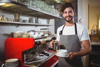 カフェカウンターでコーヒーを作るウェイターを笑顔