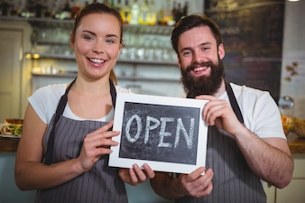 Smiling waitress and waiter standing with open sign board in cafe