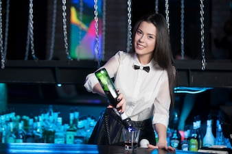 Smiling waitress preparing a glass