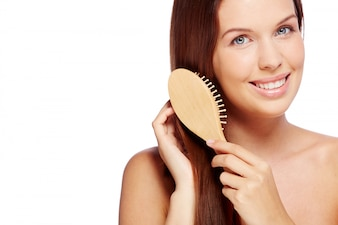 Smiling woman brushing her healthy hair