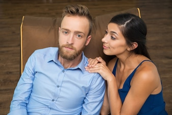 Smiling woman consoling her stressed boyfriend