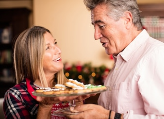 Smiling woman holding a tray with christmas cookies