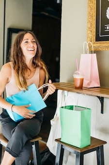 青い紙袋を持っている笑顔の女性