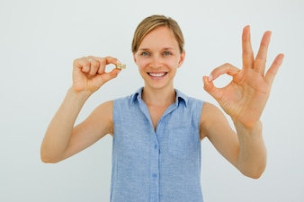 Smiling Woman Holding Coins and Showing OK Sign