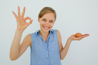 Smiling Woman Holding Egg and Showing OK Sign