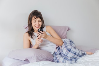 Smiling woman in bed typing on smartphone