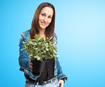 Smiling woman in denim jacket with a plant