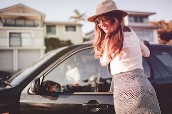 Smiling woman opening door car and looking at camera. Road trip adventure concept.
