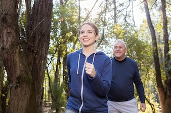 Smiling woman running with her grandfather