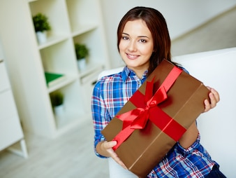 Smiling woman showing a gift with a red bow