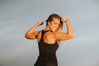Smiling woman showing strong biceps after outdoors fitness workout. Fitness girl. Back view.