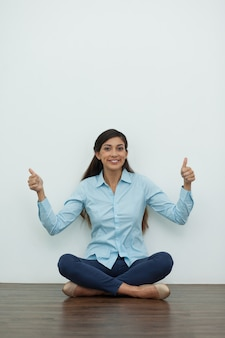 Smiling Woman Sitting on Floor with Thumbs Up