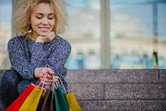 Smiling woman sitting with colorful paper bags