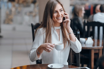 Smiling woman talking on the phone and holding a cup of coffee