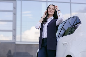 Smiling woman talking on the phone leaning on a car