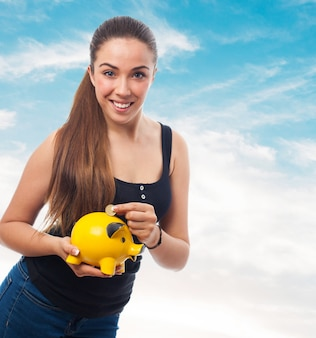 Smiling woman tossing a coin into a pig piggy bank