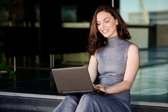 Smiling woman using her laptop sitting in a modern place