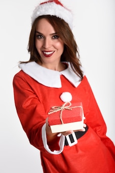 Smiling woman wearing santa claus clothes with a gift box