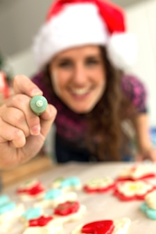 Smiling woman with a coloring pencil for cookies