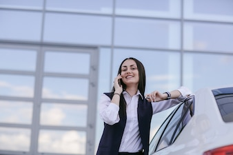 Smiling woman with an elbow leaning on a car while talking on the phone