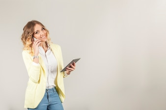 Smiling woman with smartphone and tablet