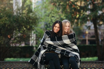 Smiling women embracing in plaid