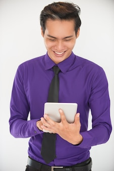 Улыбаясь молодых азиатских бизнес человек с помощью планшета