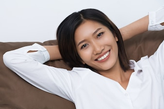 Smiling Young Asian Woman Lying on Cushion