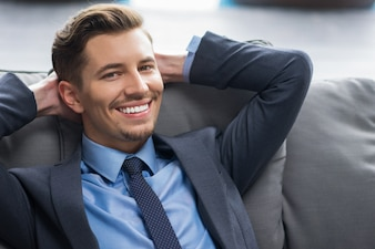 Smiling Young Businessman with Hands Behind Head