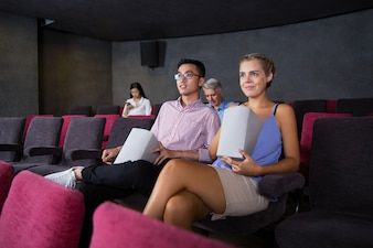Smiling young couple watching film in cinema