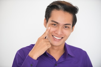 Smiling Young Handsome Asian Man Pointing to Eye