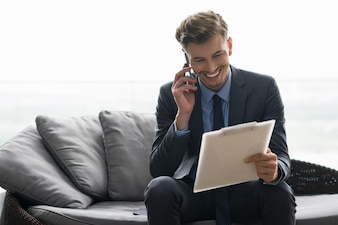 Smiling Young Man Discussing Document on Phone