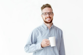 Smiling young manager in glasses drinking coffee