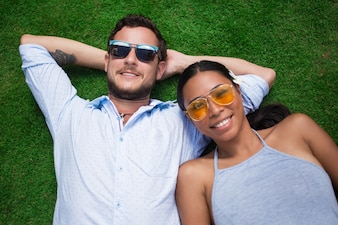 Smiling Young Multi-ethnic Couple Lying on Lawn