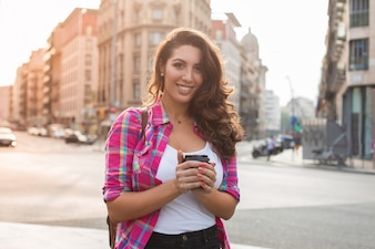 Smiling young woman holding coffee cup outdoors