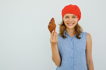 Smiling Young Woman Holding Delicious Croissant